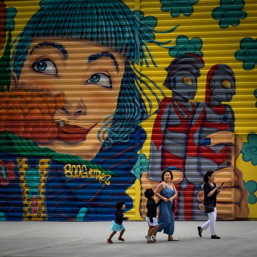 Family walking past a colorfull mural in Manhattan New York.
