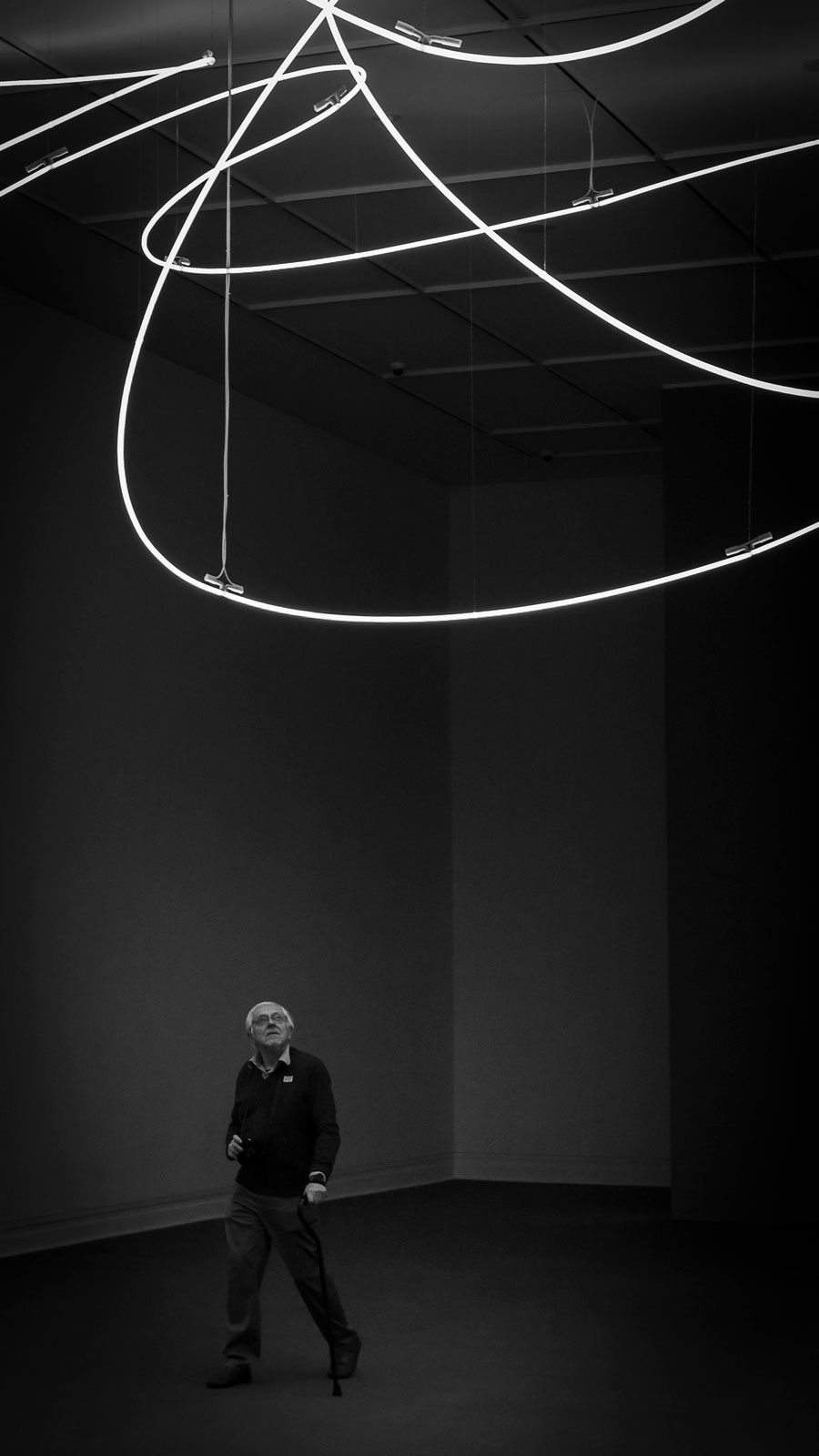 Man looking up at a neon installation at the Met